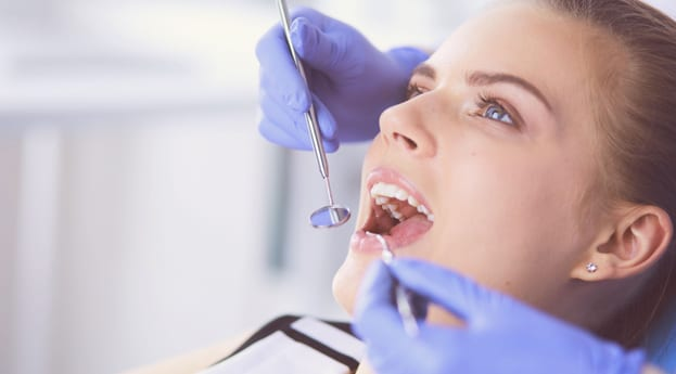 Ashley Smitherman checks a Female patient for cavities at Perspective Dental