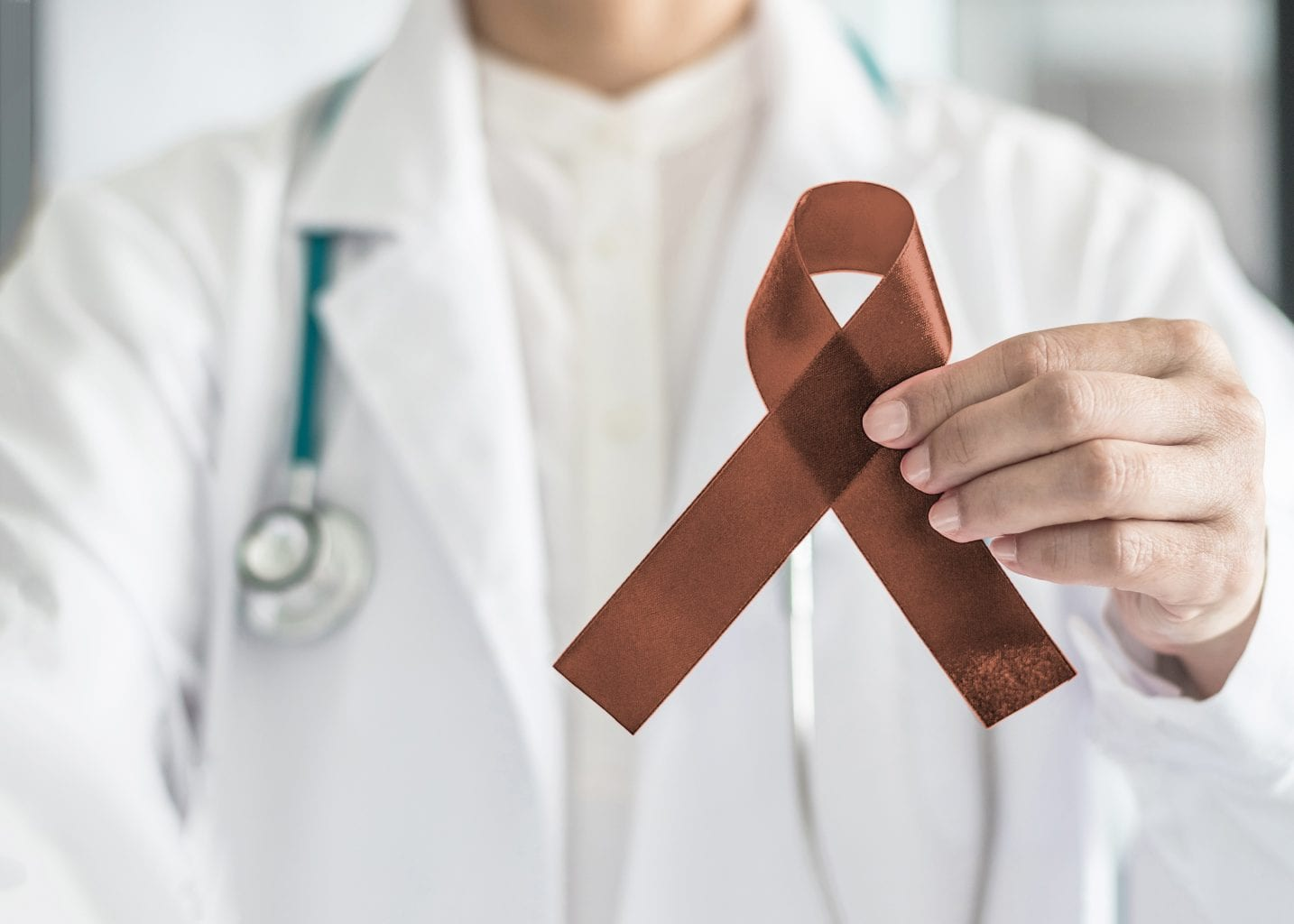 Copper Brown Awareness Ribbon On Doctor's Hand, Symbolic Color For Anti Tobacco, Colon Colorectal Cancers, Herpes Simplex Virus (hsv 1 And Hsv 2)